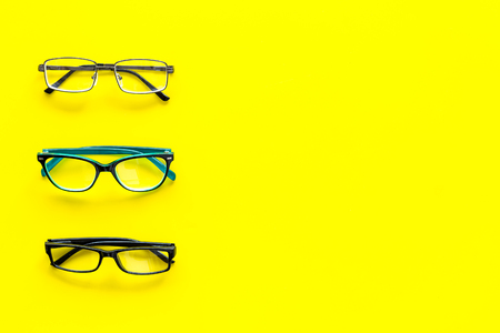 Glasses concept. Set of glasses with different eyeglass frame and transparent lenses on yellow background top view copy space pattern Reklamní fotografie