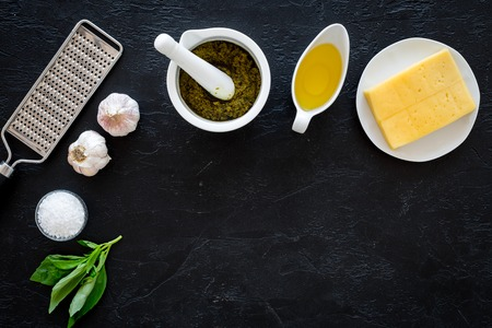 Ingredients for pesto sauce. Cheese, garlic, green basil, olive oil, sait near grater and mortar on black background top view space for text
