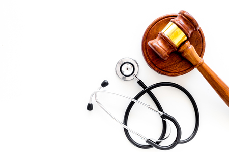 Medical law, health law concept. Gavel and stethoscope on white backgound top view copy space