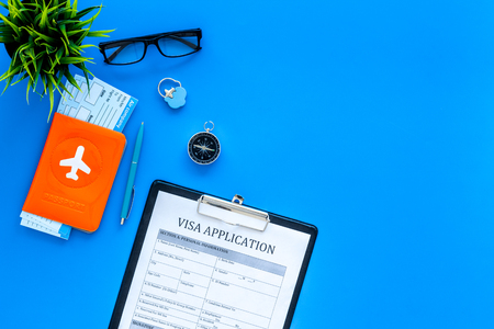 Planning vacation. Visa prosessing. Airplane tickets near passport cover with airplane silhouette, visa application form, compas on blue background top view copy space Archivio Fotografico - 103836278