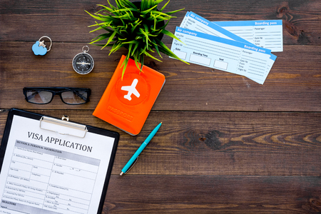 Prepare to trip. Do visa. Airplane tickets near passport cover with airplane silhouette, visa application form, compas on dark wooden background top view copy space