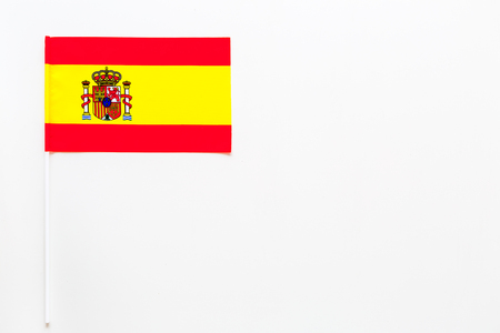Spanish flag concept. Small flag on white background top view copy space