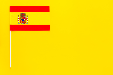 Spanish flag concept. Small flag on yellow background top view copy space Reklamní fotografie - 103864117