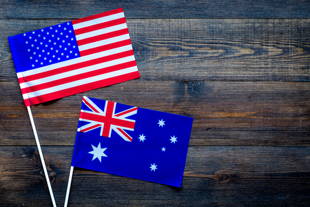 USA-Australia relations. Country cooperation. American and Australian flags on dark wooden background top view copy space