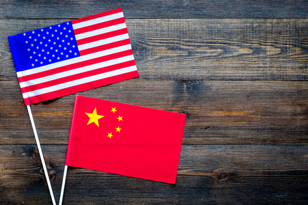 USA-China relations. Country cooperation. American and Chinese flags on dark wooden background top view copy space Stock Photo