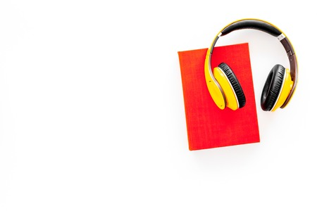Books online concept, audiobooks. Spend leasure time reading and listening music. Headphones near hardback book with empty cover on white background top view.