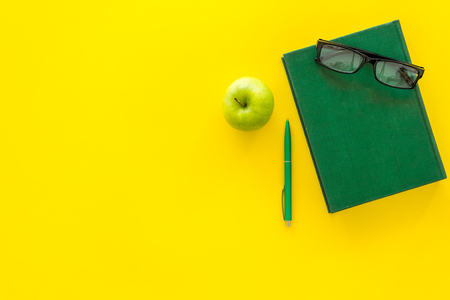 Educational literature. School textbook, book, tutorial, apple and glasses on yellow background top view.