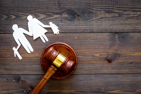 Family law, family right concept. Child-custody concept. Family with children cutout near court gavel on dark wooden background top view. Stockfoto - 103894745