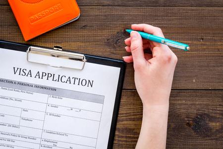 Hand fills visa application form on dark wooden background top view.