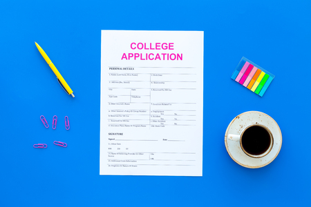 Higher education. College application form ready to fill near coffee cup and stationery on blue background top view.