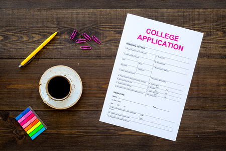 Higher education. College application form ready to fill near coffee cup and stationery on dark wooden background top view.