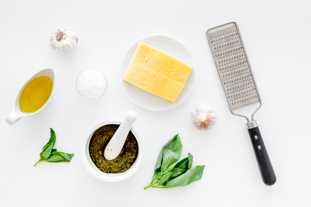 Ingredients for pesto sauce. Cheese, garlic, green basil, olive oil, salt near grater and mortar on white background top view. Stock Photo
