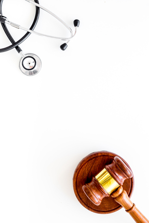 Medical law, health law. Gavel and stethoscope on white backgound top view.