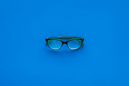 One glasses with transparent lenses on blue background top view. Reklamní fotografie - 103894831
