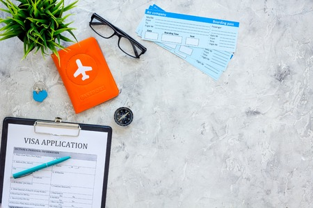 Planning vacation. Visa prosessing. Airplane tickets near passport cover with airplane silhouette, visa application form, compas on grey background top view. Archivio Fotografico - 103894848