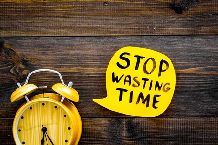 Stop wasting time hand letterng in cloud near alarm clock on dark wooden background top view copy space. Business concept, motivation.