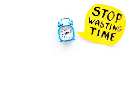 Stop wasting time hand letterng near alarm clock on white background top view copy space. Business concept, motivation.