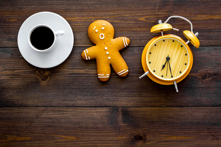 Time loss concept. Gingerbread man near alarm clock on dark wooden background top view.