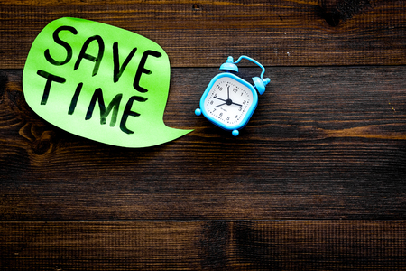 Time-management. Save time hand letterng in cloud near alarm clock on dark woodem background top view. Stock Photo