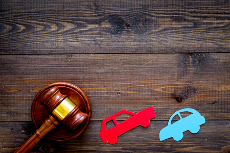 Car accident lawsuit concept. Two collided cars near judge gavel on dark wooden background top view. 스톡 콘텐츠
