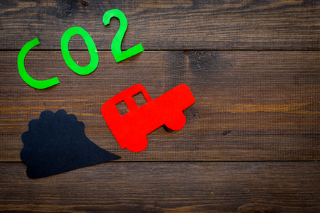 Car exhaust, co2, smoke. Car and smoke cutout on dark wooden background top view