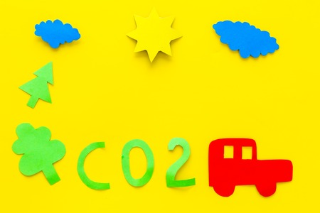 Car pollutes the environment by carbon dioxide. Car, environment and CO2 cutout on yellow background top view. Stok Fotoğraf