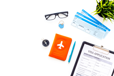 Documents for travel abroad. Visa application form, pen, passport cover with airplane silhouette on white background top view.