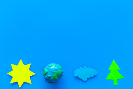 Environment protection concept. Plasticine symbol of planet Earth and sun, cloud, tree cutout on blue background top view.