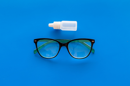 Eye drops in small bottle near glasses on blue background top view. Stock Photo - 103994566