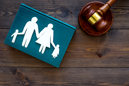 Family law, family right concept. Child-custody concept. Family with children cutout near court gavel on dark wooden background top view. Foto de archivo - 103994565