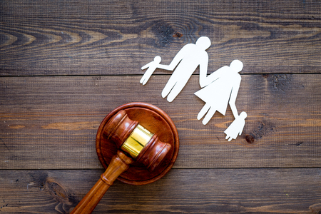 Family law, family right concept. Child-custody concept. Family with children cutout near court gavel on dark wooden background top view. Foto de archivo - 103994568