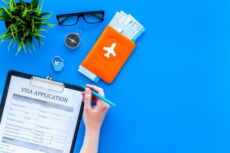 Hand fills visa application form. Form near glasses, pen, passport cover with airplane sign and airplane tickets on blue background top view. Archivio Fotografico - 103994704