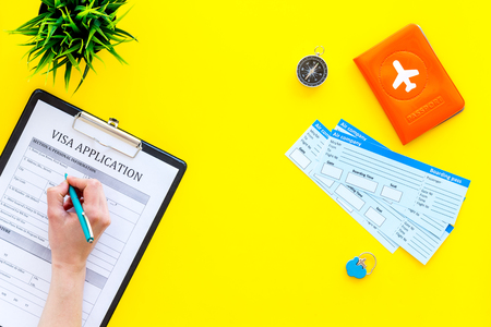 Hand fills visa application form. Form near glasses, pen, passport cover with airplane sign and airplane tickets on yellow background top view. Archivio Fotografico - 103994705