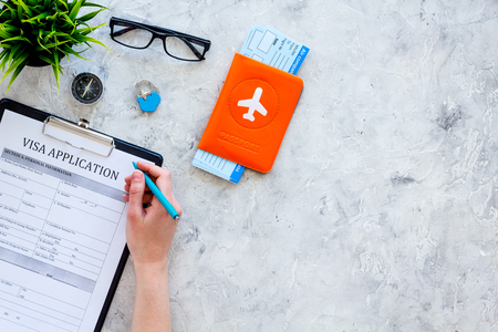 Hand fills visa application form. Form near glasses, pen, passport cover with airplane sign and airplane tickets on grey background top view.