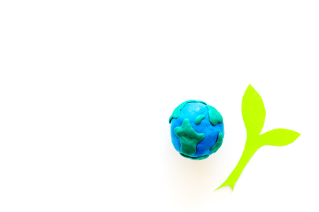 Planet, ecology. Plasticine symbol of planet Earth globe and plant cutout on white background top view. Imagens