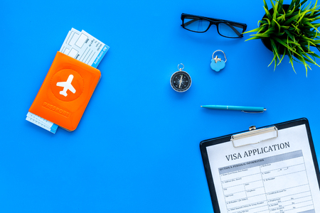 Planning vacation. Visa processing. Airplane tickets near passport cover with airplane silhouette, visa application form, compass on blue background top view.