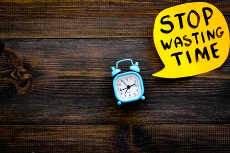 Stop wasting time hand lettering in cloud near alarm clock on dark wooden background top view copy space. Business concept, motivation.