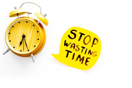 Stop wasting time hand lettering near alarm clock on white background top view copy space. Business concept, motivation. Stock Photo