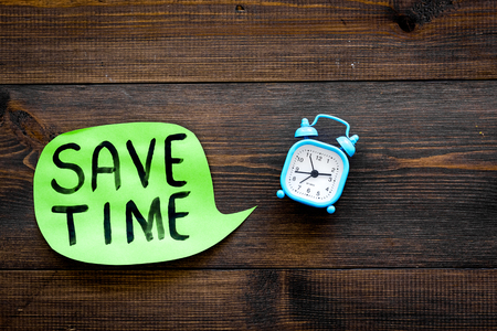 Time-management. Save time hand lettering in cloud near alarm clock on dark wooden background top view. Stock Photo