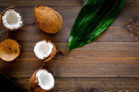 Composición tropical con coco. Cocos enteros y coco cortados por la mitad cerca de las hojas de palma en la vista superior del fondo de madera oscura.