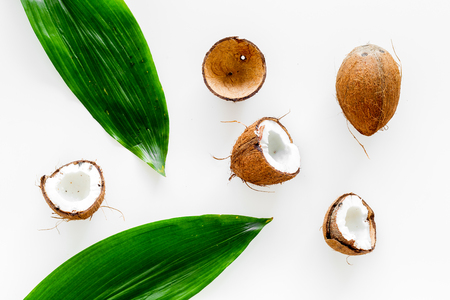 Tropical composition with coconut. Whole coconuts and coconut cut in half near palm leaves on white background top view.
