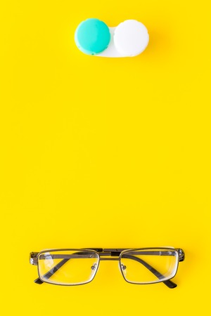 Way to improve vision. Contact lenses in container near glasses on yellow background top view. Standard-Bild