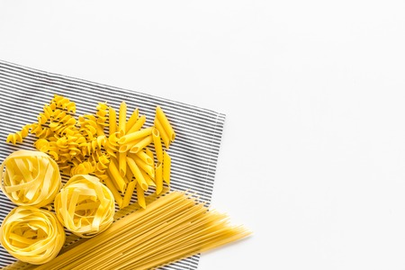 Assortment of raw pasta. Spaghetti, fusilli, penne, fettuccine on blue tablecloth on white background top view.