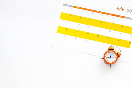 Deadline concept. Alarm clock on calendar on white background top view. Stockfoto