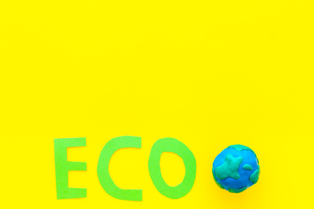 Eco icon cutout near planet Earth Plasticine symbol on yellow background top view.
