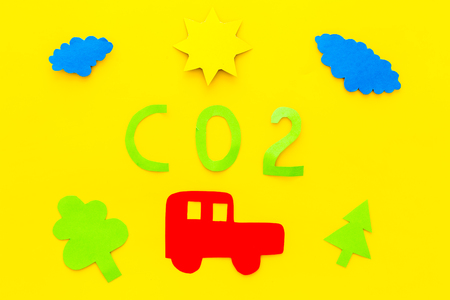 Car pollutes the environment by carbon dioxide. Car, environment and CO2 cutout on yellow background top view. Reklamní fotografie