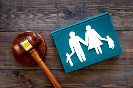 Family law, family right concept. Child-custody concept. Family with children cutout near court gavel on dark wooden background top view. Stockfoto - 104081045