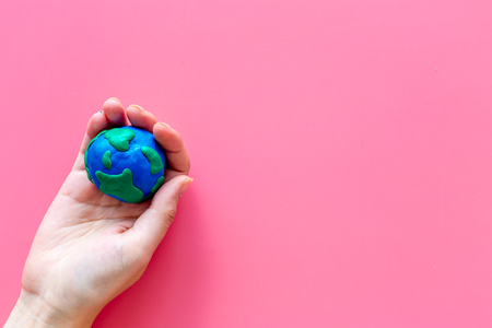Earth. Hand hold Plasticine symbol of planet Earth globe on pink background top view.