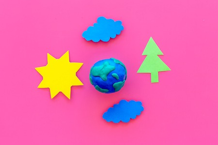Environment protection concept. Plasticine symbol of planet Earth and sun, cloud, tree cutout on pink background top view.