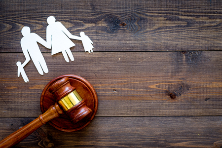 Prawo rodzinne, pojęcie prawa rodzinnego. Pojęcie opieki nad dzieckiem. Rodzina z dziećmi wyłącznik w pobliżu dworu młotek na ciemnym drewnianym tle widok z góry. Zdjęcie Seryjne
